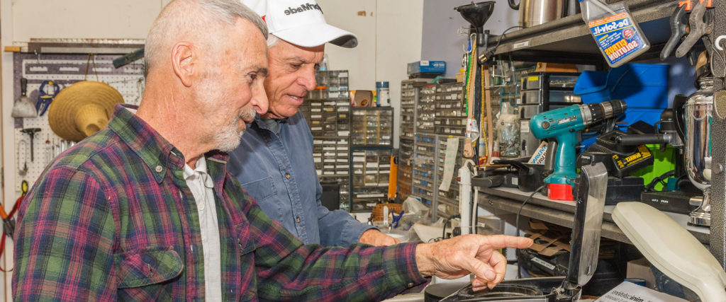 2 volunteers prepare electronics for re-sale